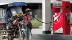 A petrol station worker fills a 'tuk-tuk'