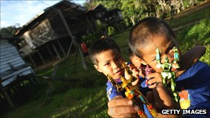 Boys hold toy robots outside their house in Sarawak