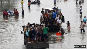 "People are evacuated on trucks from a flooded area in Bangkok""s suburbs October 20, 2011"