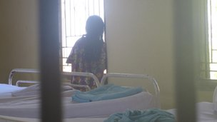 A female patient being locked behind bars at the Lawang Mental Hospital