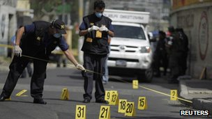 Agents of the Public Ministry investigate at the crime scene where two men were shot and killed in a go-kart in Guatemala City October 7, 2011
