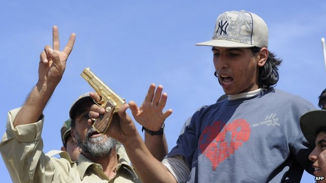 Libyan fighter brandishes a pistol
