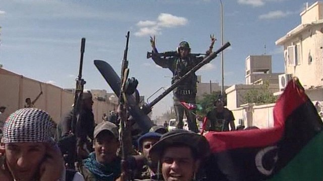 Libyan fighters in Sirte celebrate reports that Gaddafi is dead