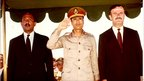 Libyan leader Muammar Gaddafi salutes, beside Egyptian President Anwar Sadat (left) and Syrian President Hafez Assad (right) during a military parade in May 1971