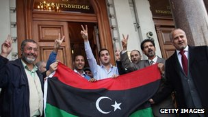 People gather outside the Libyan embassy in London