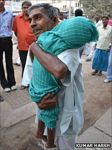 A man holding the body of a child who died of encephalitis at a Gorakhpur hospital