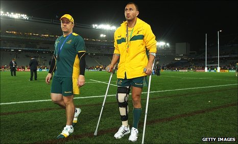 Quade cooper leaves the stadium on crutches with his knee in a brace