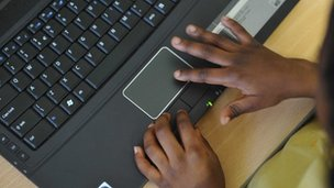 A black pupil's hands on a laptop