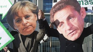 Protesters dressed as German Chancellor Angela Merkel and French President Nicolas Sarkozy