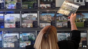 Woman looking in estate agent&#039;s window