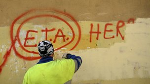 "A municipal worker paints over graffiti reading ""ETA, The People Are With You"" in Guernica October 21, 2011"