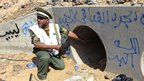 An NTC fighter looks through a large concrete tunnel where Col Gaddafi was allegedly captured. Photo: 20 October 2011