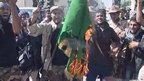 Green flag of Muammar Gaddafi burned by interim government troops, 20 Oct