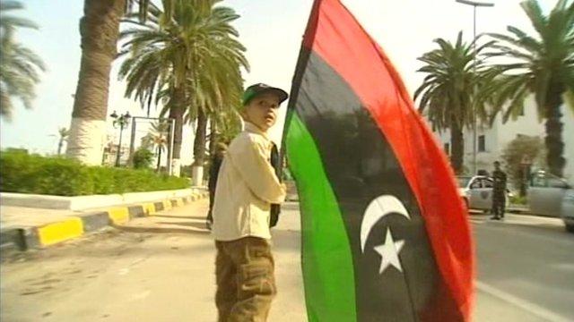 A boy holding a Libyan flag