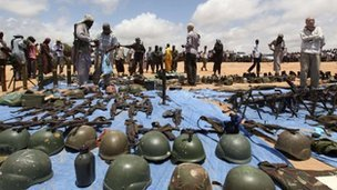 Islamic militants display weapons and equipment of African soldiers they killed in clashes in Mogadishu
