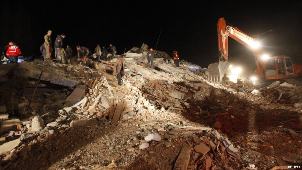 A digger helps searchers work through the rubble of a building in the town of Ercis, Turkey - 23 October 2011