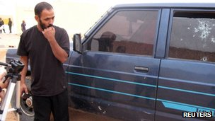 A man looks at shots in a window of a car which was used to try to stop kidnappers in Tindouf on 23 October 2011.