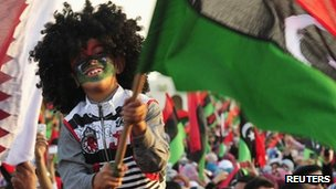 A child celebrates with a flag in Benghazi, 23 October