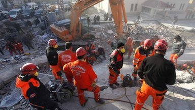 Emergency service workers work to save people trapped under debris after the earthquake in Ercis province