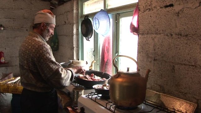 A manual worker in Tehran, makes food for a group of fellow workers. Dozens of them live in this shack.