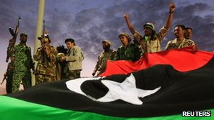 Anti-Gaddafi fighters gesture to the crowds during celebrations for the liberation of Libya in Quiche, Benghazi October 23, 2011