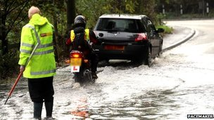 DoE worker in flooded road with motorcycle and car