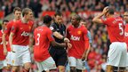 Manchester United players protest to referee Mark Clattenburg after he sends off Manchester United's Northern Ireland defender Jonny Evans