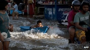 A boy in a boat is towed up a Bangkok street by a motor bike