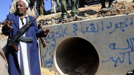 A fighter at the drainage pipe where Col Muammar Gaddafi was captured