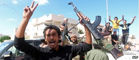 A fighter celebrates after Col Gaddafi's capture