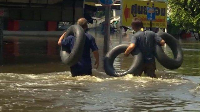 Men wading through thigh-deep water just north of Bangkok