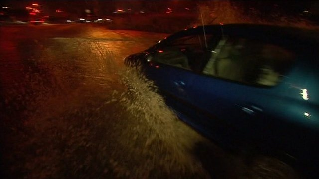 Car attempts to move along flooded road