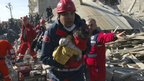 A rescue worker carrying a girl runs to an ambulance after his team found her alive in a collapsed building in Ercis, 24 October 2011
