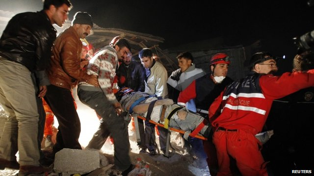 An earthquake survivor is carried by rescue workers from a collapsed building