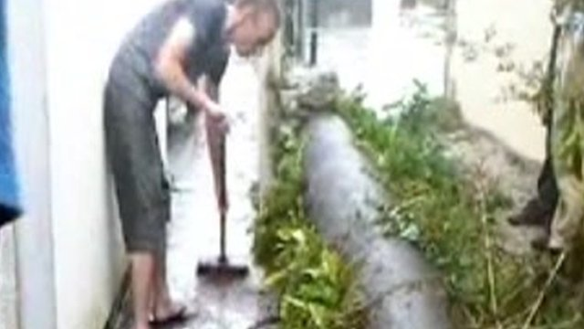 A resident sweeps raw sewage from his garden