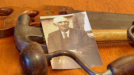 A photograph of John Flynn beside the tools of his trade