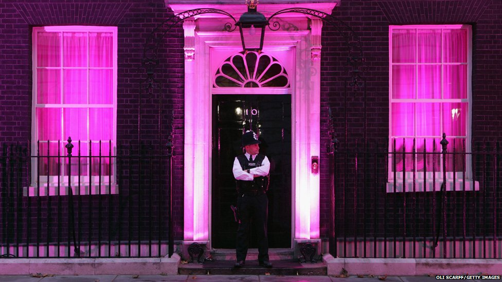 A police officer stands in front of 10 Downing Street, London, which is illuminated in a pink light  in support of Breast Cancer Awareness Month