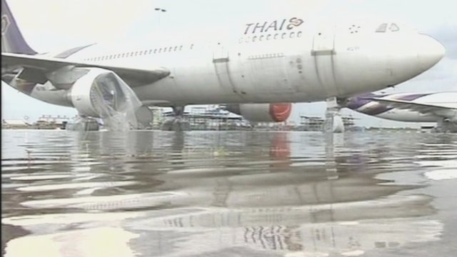 Plane stands in water at Don Muang airport, Bangkok