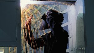 welder stands in a shower of sparks