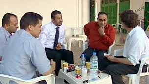 Libyans talk to Gabriel Gatehouse (right) at a cafe in Misrata