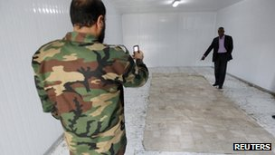 An anti-Gaddafi fighter takes a picture inside the storage freezer where Col Gaddafi's body was kept in Misrata