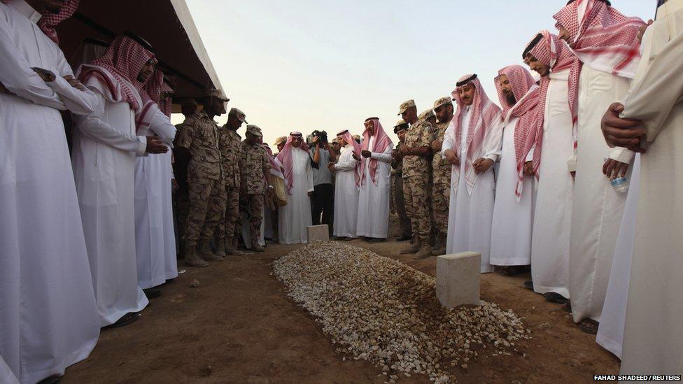 Saudi men gather around a grave