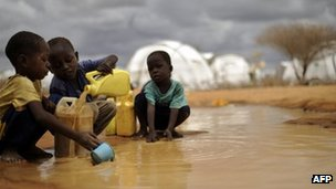 Somali boys fetching water from a puddle in Dadaab refugee camp in Kenya