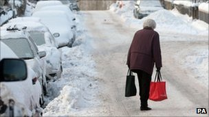 Elderly woman walking through the snow in Peebles last winter