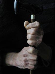 Old hands holding walking stick