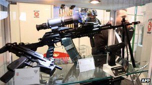 A man walks past guns on display at an exhibition for Libya's Defense, Security and Safety (file photo 2010)