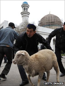 Kazakh Muslims drive sheep for slaughter outside a mosque in Almaty