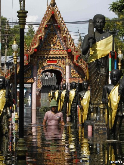 Man walking through a flooded temple in Bangkok's Don Muang district
