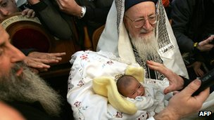 Israel's Rabbi Mordechai Eliyahu carries an eight-day-old baby during a circumcision ceremony in front of the Knesset (Israeli Parliament) in Jerusalem 10 January 2004.