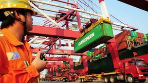 A worker monitors the loading of containers in Qingdao, China